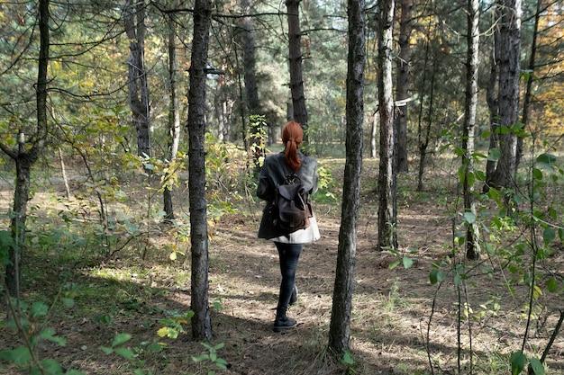 Активная красивая рыжеволосая девушка гуляет по лесу. свежий открытый лес, концепция здорового образа жизни