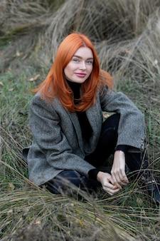 Активная красивая рыжеволосая девушка гуляет по лесу. самоизоляция на свежем воздухе. девушка, сидящая одна в зеленом лесу, наслаждается тишиной и красотой природы.