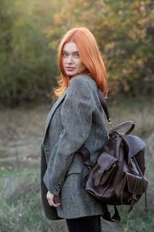 Активная красивая рыжеволосая девушка гуляет по лесу. женщина-путешественница с рюкзаком идет по удивительному лесу, концепции путешествия, пространству для текста, атмосферному моменту. день земли