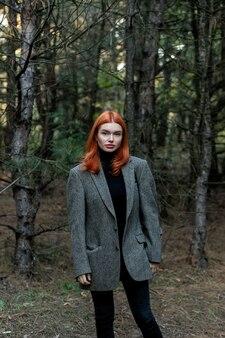 Активная красивая рыжая девушка гуляет по лесу