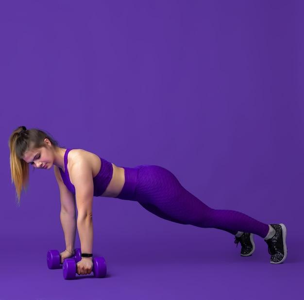 유효한. 스튜디오에서 연습하는 아름다운 젊은 여성 운동선수, 단색 보라색 초상화.