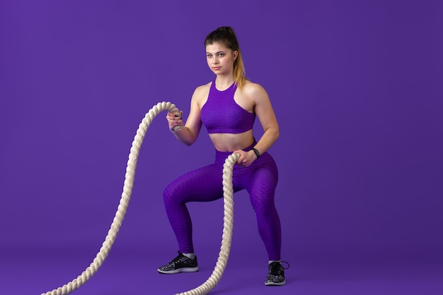 Active. beautiful young female athlete practicing , monochrome purple portrait. sportive caucasian fit model with ropes. body building, healthy lifestyle, beauty and action concept.