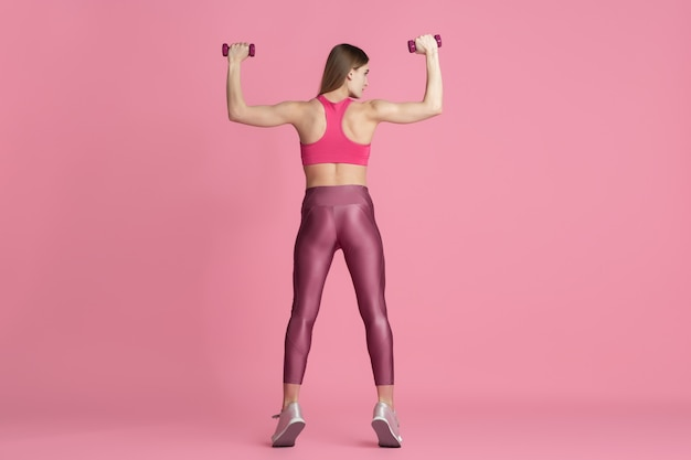Active. beautiful young female athlete practicing in studio, monochrome pink portrait.