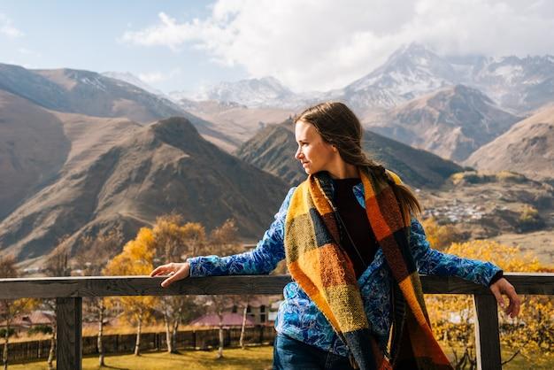 暖かいジャケットを着たアクティブな美しい少女は、雄大な山々を背景に立って、自然ときれいな空気を楽しんでいます
