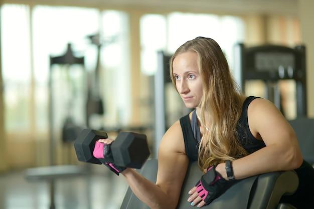 ジムでアクティブな美しい若い女性のトレーニング
