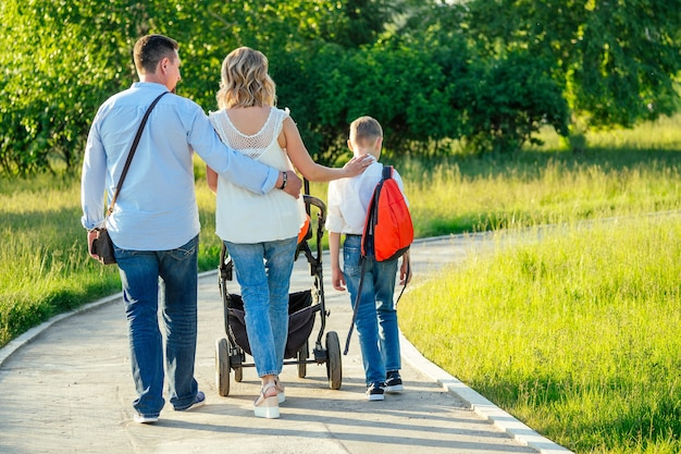 Активный большой семейный отец, мать, сын и ребенок в прогулочной коляске в парке сзади.
