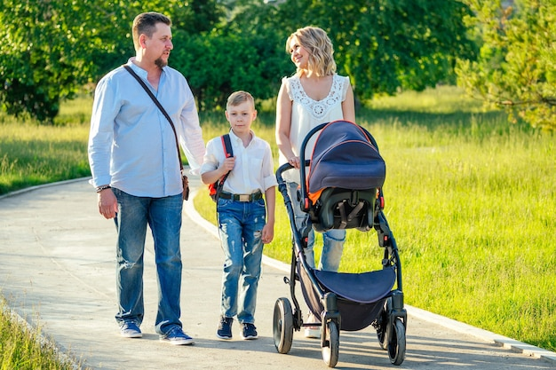 公園を歩いているベビーカーでアクティブな大家族の父、母、息子、赤ちゃん