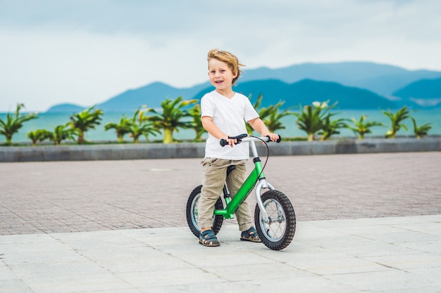 Active blond kid boy driving bicycle in the park near the sea