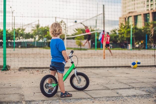 海の近くの公園で自転車でアクティブな金髪の子供男の子