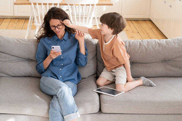 활동적인 지루한 작은 아들은 집에서 스마트폰으로 온라인 작업을 하는 젊은 어머니 사업가의 주의를 산만하게 합니다.