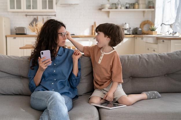 Активный скучающий маленький сын отвлекает молодую мать-предпринимательницу на работу онлайн на смартфоне из дома
