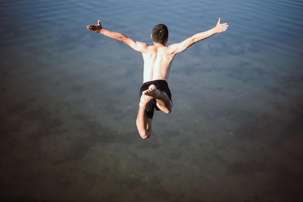 Активный мальчик прыгает в воду
