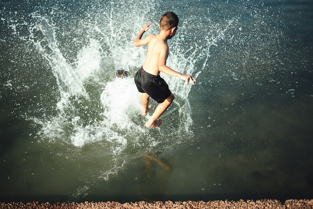 Active boy jumping into the water