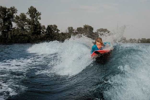 Active boy lying on wakeboard and swimming down the river