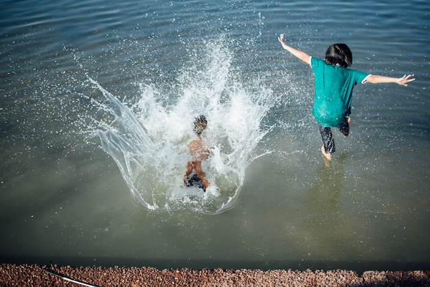 Active boys jumping from logs into water.