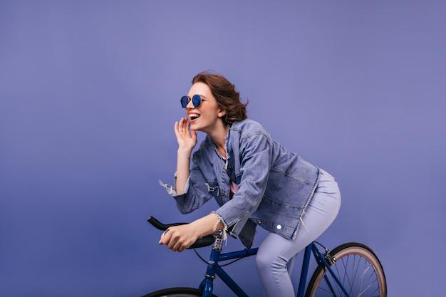 Ragazza castana attiva che guida sulla bici. foto interna della signora allegra in giacca di jeans che si siede sulla bicicletta.