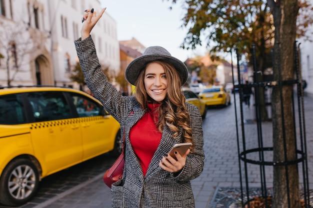 La donna attiva di affari indossa un lungo cappotto di tweed che si affretta in ufficio con un sorriso felice