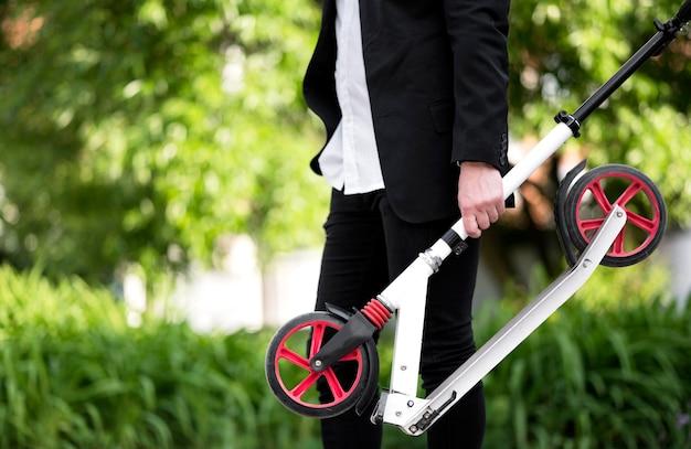 Активный бизнесмен, перевозящих скутер на открытом воздухе