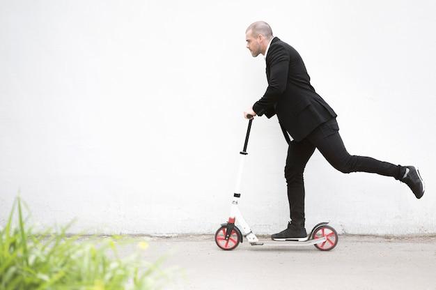 Активный бизнесмен езда скутер на открытом воздухе