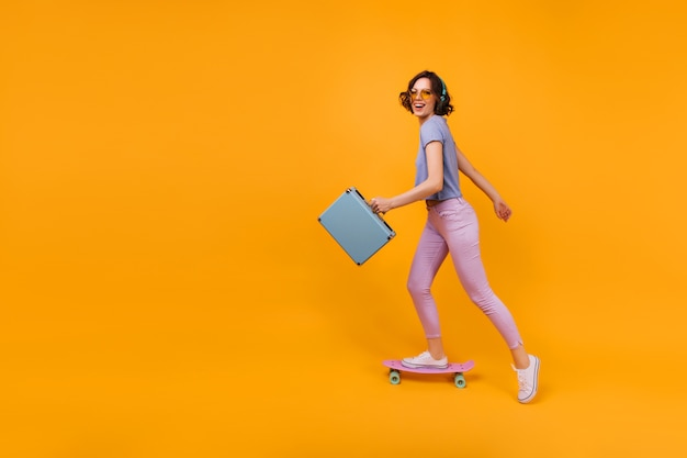 スーツケーススケートでアクティブな白人女性。ロングボードに立っている壮大な巻き毛の女の子の屋内ショット。