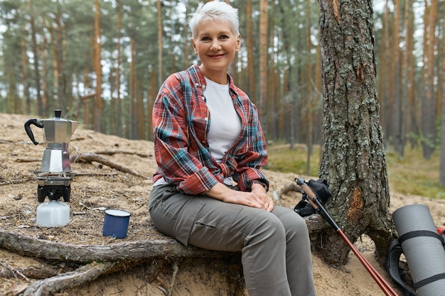 長距離トレッキング中に小さな休憩をとって、ガスストーブバーナーでお茶のためにキャンプ用品の沸騰したお湯で木の下に座っているアクティブな陽気な中年の女性。人、冒険、旅行、ハイキング