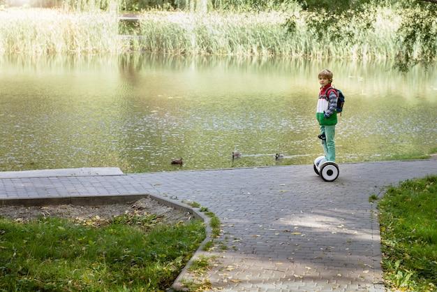 秋のきれいな湖の都市公園でモダンな白い電子ホバーボードに乗ってアクティブな子供