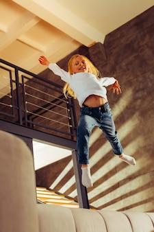 活発な子供時代。うれしそうな未就学児がソファに飛び乗り、家で週末を楽しんでいる