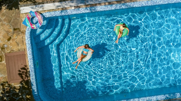 上からスイミングプールの空中上面でアクティブな子供、幸せな子供はインフレータブルリングドーナツで泳ぐし、リゾートで家族での休暇中に水で楽しい時を過す