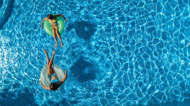 上からのスイミングプールの空中上面図でアクティブな子供たち、幸せな子供たちは膨らませてリングドーナツで泳ぎ、リゾートでの家族の休日の休暇で水で楽しんでいます
