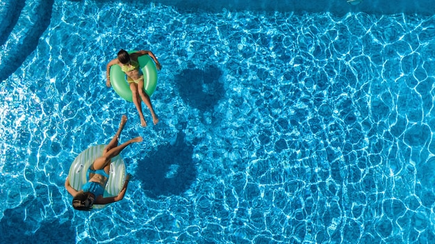Active children in swimming pool aerial top view from above, happy kids swim on inflatable ring donuts and have fun in water on family holiday vacation on resort