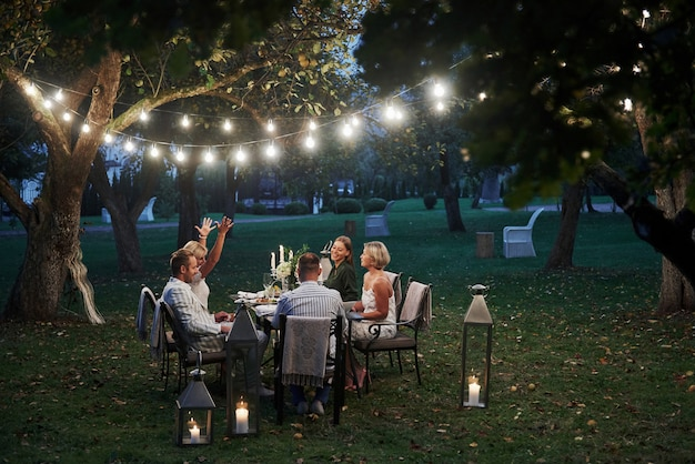 アクティブな会話。イブニングタイム。友達は豪華な屋外の場所で夕食をとります
