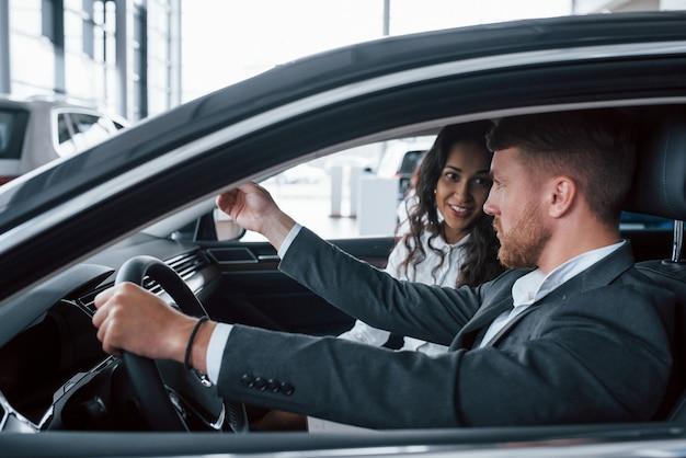 활발한 대화. 자동차 살롱에서 새 차를 시도하는 사랑스러운 성공적인 부부