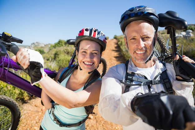 Active couple carrying their bikes on country terrain together on a sunny day