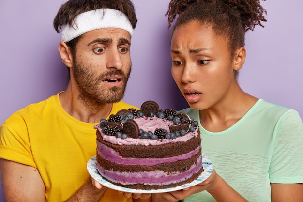Active couple posing with a big cake