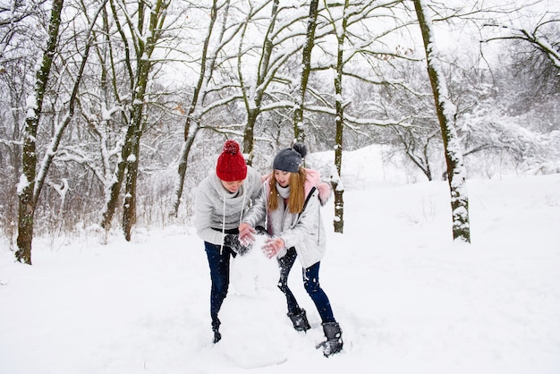 Active couple of teenagers making snowman