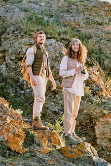 Active couple walking over stone rocks