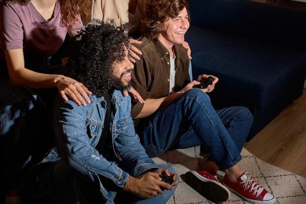 自宅でゲームパッドを手にゲーム機でビデオゲームを楽しんでいる活発なカップルの友人、床にいる男性がゲームに参加し、ガールフレンドが彼らをサポート