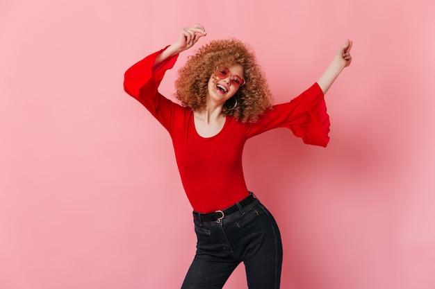 Активная кудрявая дама в солнечных очках, красном топе с длинными рукавами и джинсовых брюках смеется и танцует на розовом пространстве.