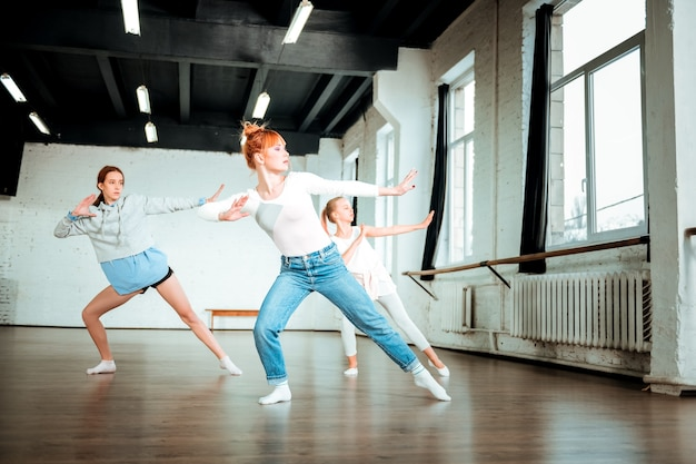 Активный танец. рыжая учительница танцев в синих джинсах и ее ученики танцуют в студии