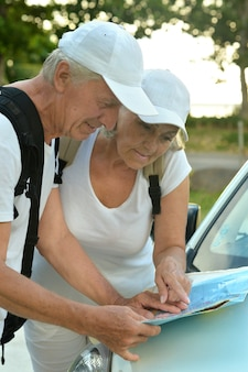 Active elderly couple looking at travel map