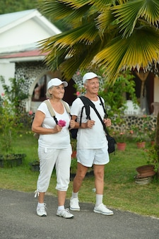 Active elderly couple with backpacks in the journey