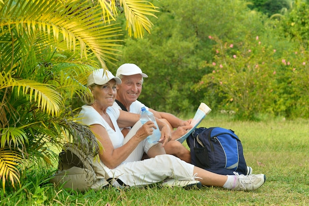 Active elderly couple with backpacks resting sitting on the grass