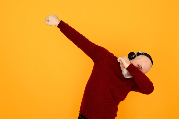 Активный энергичный бородатый дедушка в беспроводных наушниках слушает музыку. веселый старший мужчина танцует под радио в наушниках bluetooth, вытирает, делает танцевальное движение, глядя из-под его руки