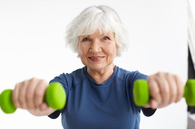 실내에서 운동을 즐기는 회색 머리를 가진 활성 정력적 인 행복 노인 백인 여성, 아령을 사용하여 집에서 훈련, 광범위하게 미소. 여자의 얼굴에 선택적 초점