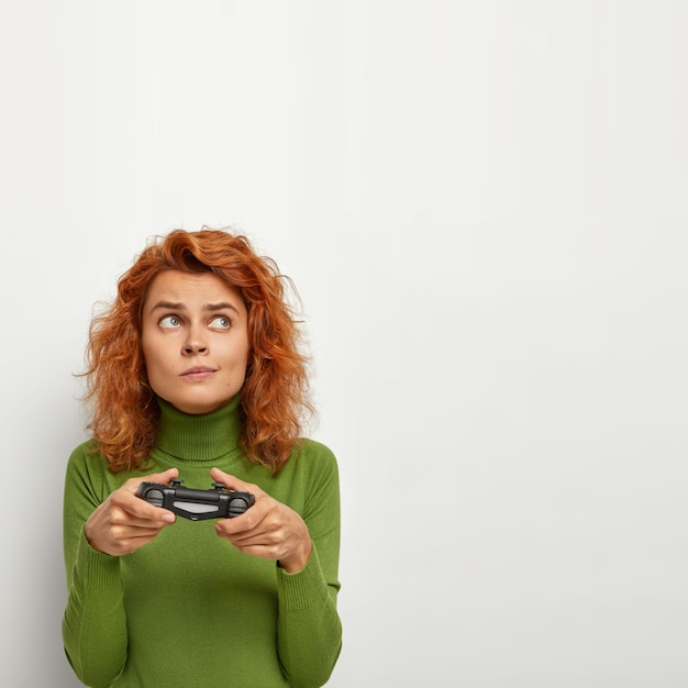 Active energetic lady with thoughtful expression, uses game console for playing video games, wears green sweater, looks aside, isolated on white wall with empty space for your promotion.