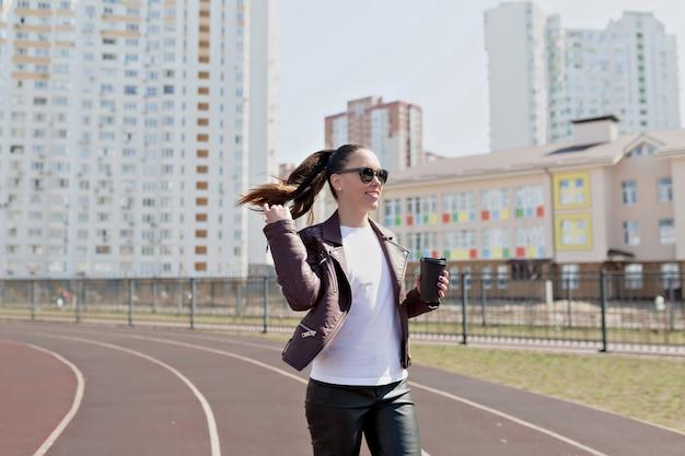 アクティブな興奮しているモダンな女性は革のジャケットを着て、白いtシャツと黒のメガネはコーヒーカップと一緒に歩く
