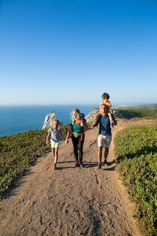 Active family couple and children  hiking along seaside, walking on path. boy riding on dads neck. full length. nature and recreation concept