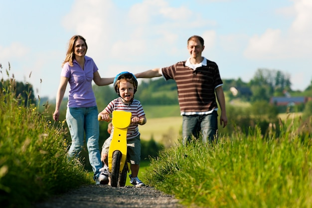 Active family in summer walking and bicycling