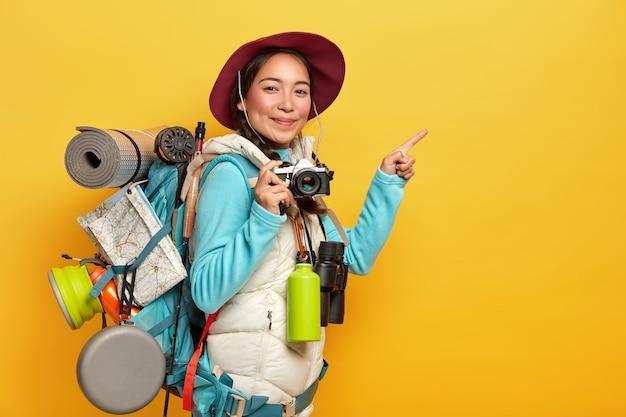 활동적인 여성 백패커는 집게 손가락을 복사 공간 옆에두고, 레트로 카메라를 들고, 사진을 찍고, 배낭, 쌍안경 및 보온병을 들고, 캐주얼 한 옷을 입습니다.