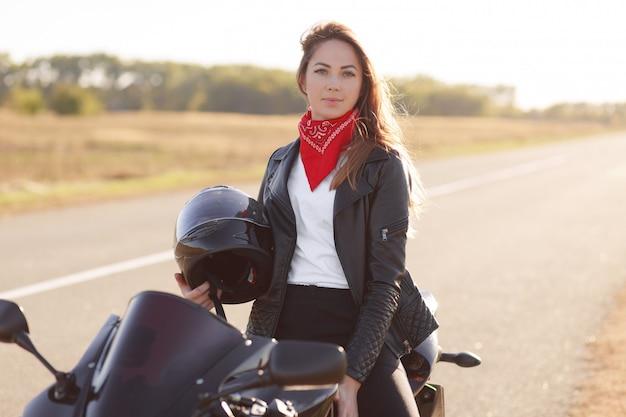 Active female driver sits on black fast motobike